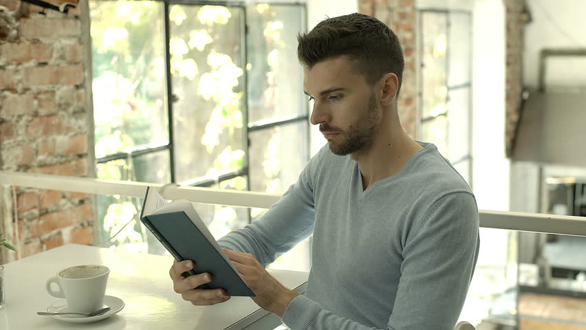 Handsome man in blue sweater looks absorbed while reading book in the cafe, steadycam shot  | Shutterstock HD Video #30992323