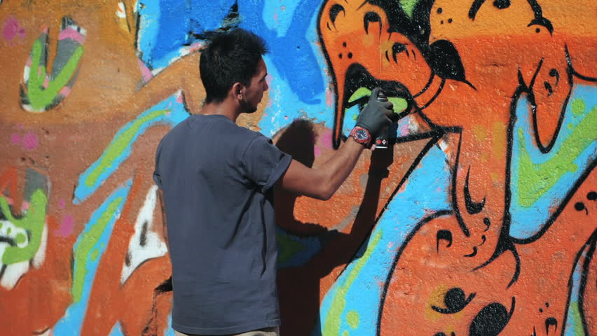 Graffiti Artist Painting With Aerosol. Man with spray bottle. Slow Motion. Young urban painter drawing colorful graffiti on the urban street wall at summer sunny day.
