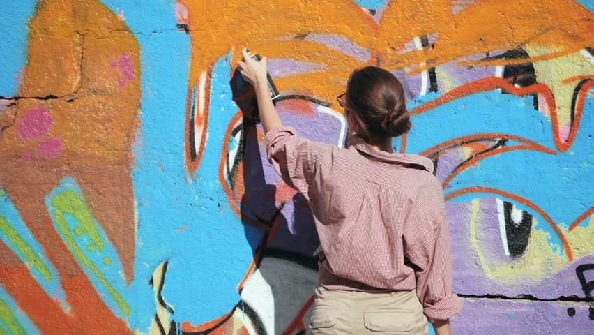 Beautiful Young Girl making a colorful graffiti with aerosol spray on urban street wall. Cinematic toned slow motion footage. Creative art. Talented student in glasses drawing picture.
