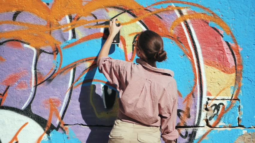 Beautiful Young Girl making a colorful graffiti with aerosol spray on urban street wall. Cinematic toned slow motion footage. Creative art. Talented woman in glasses drawing picture.