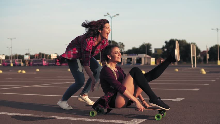 Smiling woman sitting on a longboard while her friend is pushing her behind and running during sunset. Enjoying life. Lens flare. Slowmotion shot