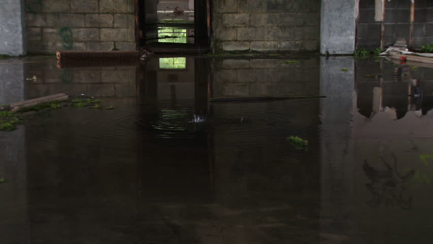 Closeup of dripping water into dark pool, which, when revealed via reverse zoom pullback, turns out to be flooded floor of decrepit abandoned urban ruin.