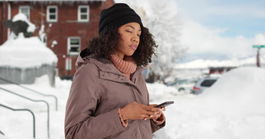 Pretty African American female removes gloves to text on cell phone outside in the snow. Cute black woman in winter coat messaging on mobile device in outdoor setting. 4k #31014679