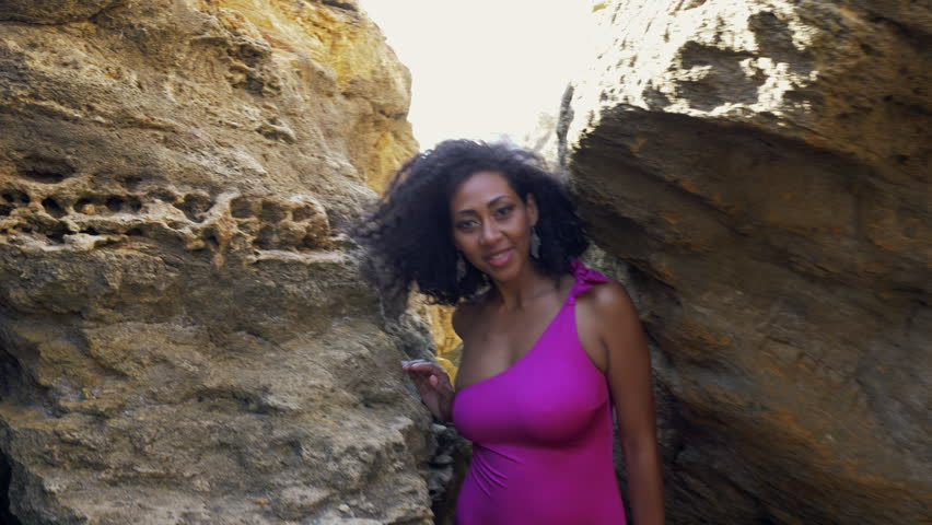 Portrait of black lady, pretty happy young african american woman looking at camera and smiling in canyon..Rocks beach.Sexy mixed race girl in pink swimsuit and jewelry enjoying nature. 4k