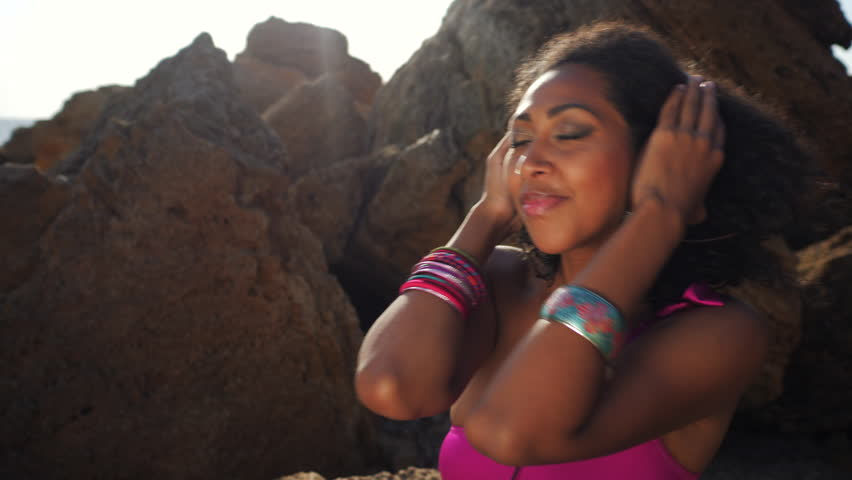 Young pretty black afro female wearing pink swimsuit and brown headphones sitting on tropical rocks beach near sea,enjoying beautiful summer day.Carefree, music concept. 4k | Shutterstock HD Video #31023310