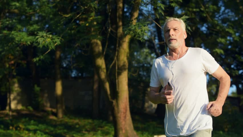 Confident senior man jogging in the park | Shutterstock HD Video #31034944