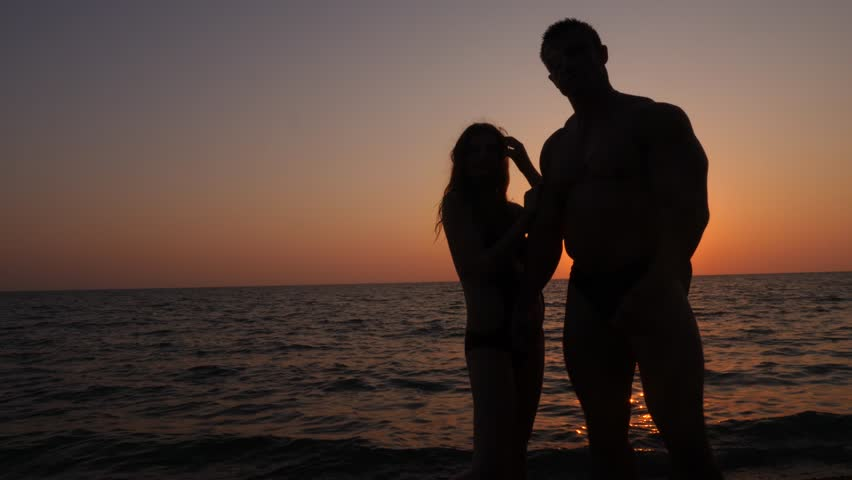 Silhouettes of pregnant women in bikini and romantic muscular man. the bodybuilder hugs, kisses his wife and strokes her belly. against the background of a sea sunset. 4k. Slow motion | Shutterstock HD Video #31036051