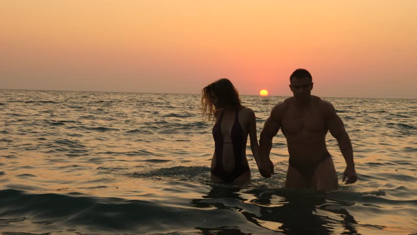 Silhouettes of pregnant women in bikini and romantic muscular man. the bodybuilder hugs, kisses his wife and strokes her belly. against the background of a sea sunset. 4k. Slow motion | Shutterstock HD Video #31036054