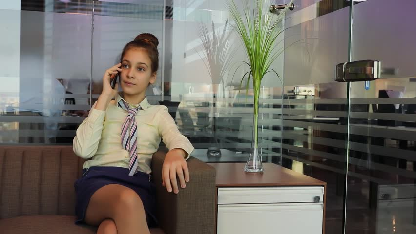 Young girl in tie sits on sofa and uses smart-phone near glass wall | Shutterstock HD Video #31038091