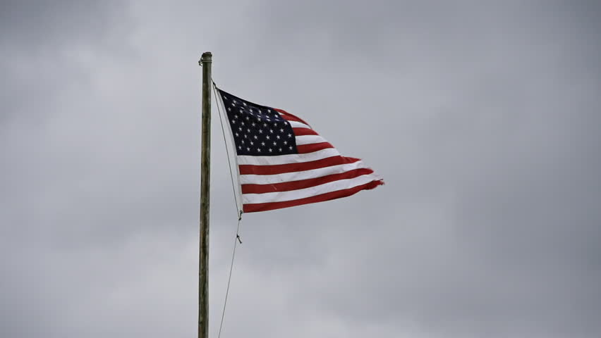 American flag in a stiff breeze, flapping and tattered becaue of exposure