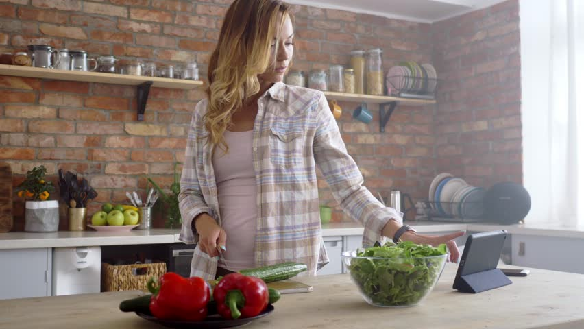 Woman looking recipe online while cooking