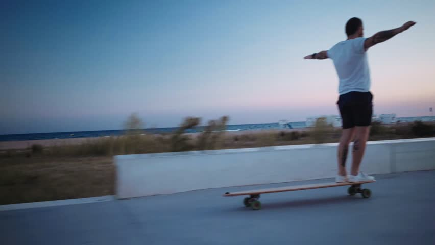 Unconventional millennial hipster extreme sports athlete with tattoos rides longboard on boardwalk next to beach during twilight sunset hour, enjoys youth and freedom #31052083
