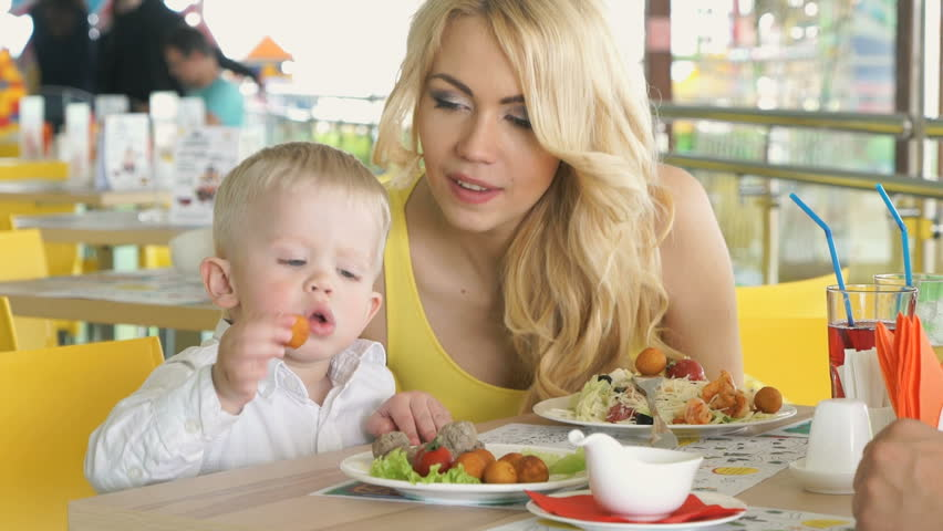 Two year-old son sitting at the table with mother indulges with food in children's cafe