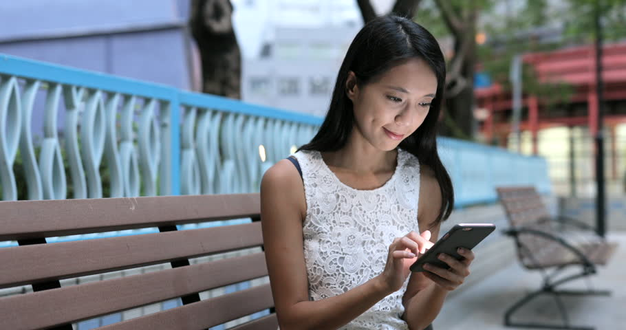 Woman using mobile phone at park | Shutterstock HD Video #31057333