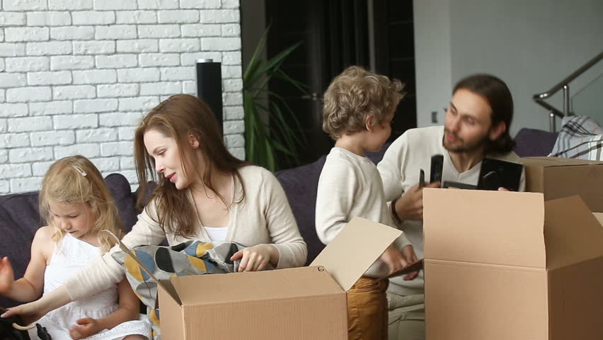 Smiling family with small son and daughter unpacking boxes together sitting on couch in modern cozy living room, happy parents playing with kids unboxing belongings after relocation into new home #31060654