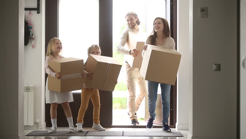 Happy family with kids holding boxes entering new modern house, excited couple and children relocating carrying belongings, opening entrance door looking around while moving in own bought rented home #31060975