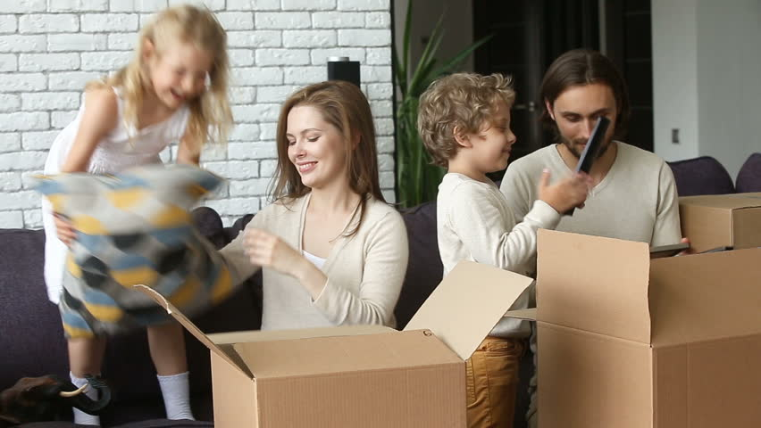 Happy excited family with two children unpacking boxes moving into new home concept, small kids helping parents with belongings in cardboards putting cushion on sofa in living room after relocation  Royalty-Free Stock Footage #31060987
