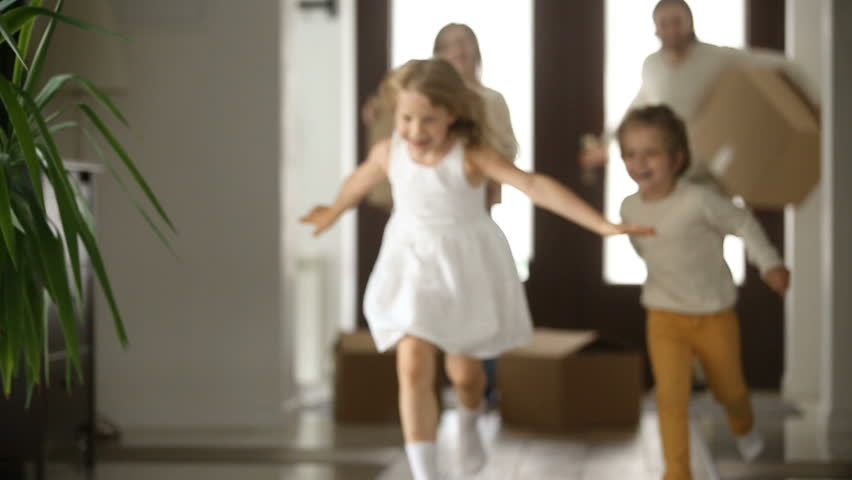 Excited kids boy and girl running into new home with parents holding boxes at background, happy couple with children and packed cardboards just moved in big modern house, family relocating concept #31060996