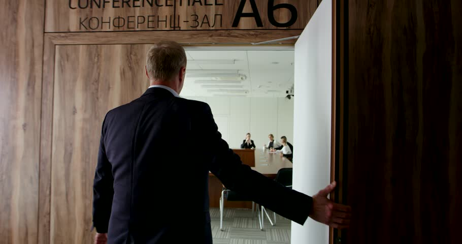 Mature businessman in formalwear entering office meeting room and shaking hands with collegue