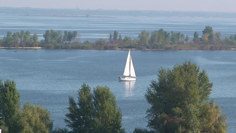 White yacht sails on the river
