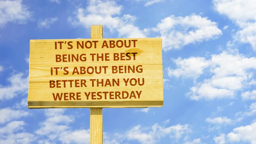 It's not about being the best, it's about being better than you were yesterday. Words on a wooden sign against time lapse clouds in the blue sky.