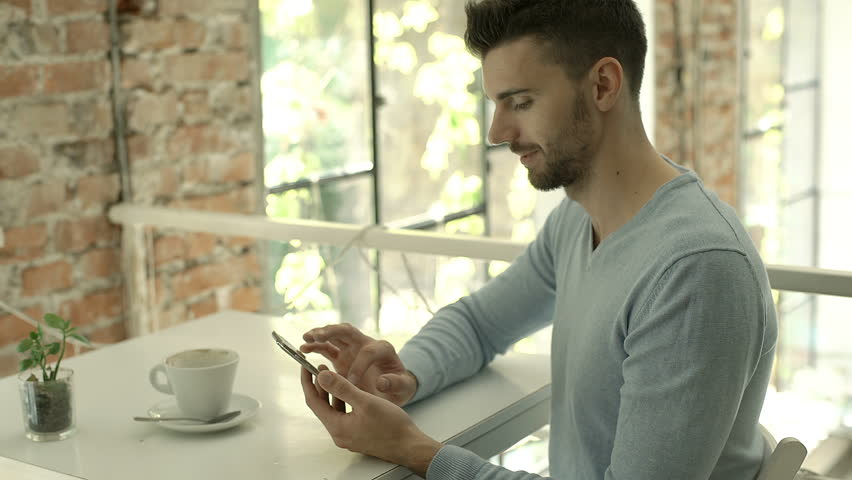 Handsome man in blue sweater browsing internet on smartphone and smiling to the camera, steadycam shot  | Shutterstock HD Video #31080541