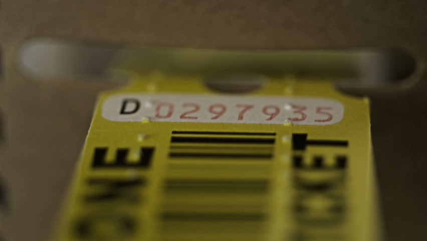 Yellow paper tickets being dispensed close up
