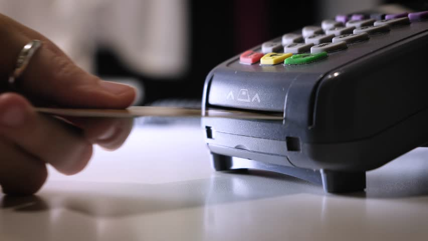A girl makes a purchase with a bank or credit card using an electronic chip in the card. Insert a card into the terminal of a non-cash payment