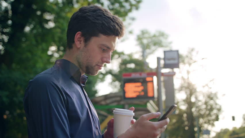 A young man sitting on a white bench in the park and using a phone. Medium shot | Shutterstock HD Video #31097752