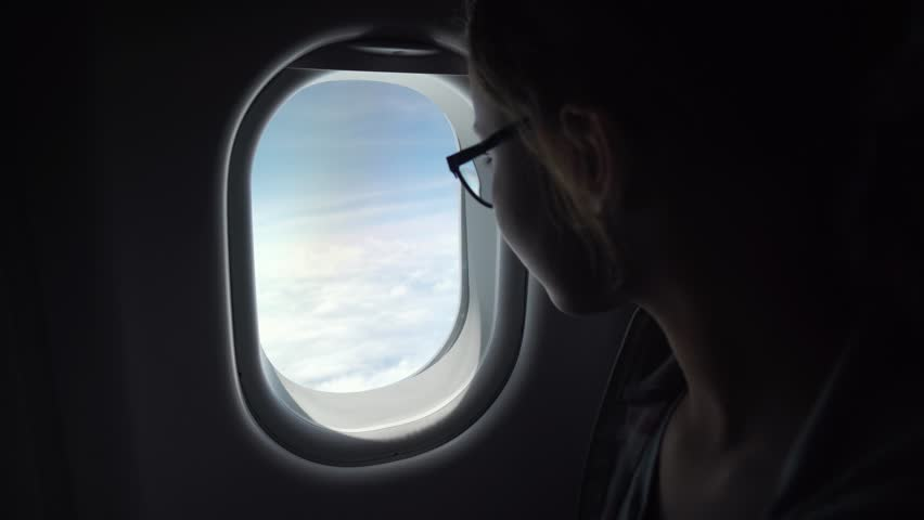 Young girl with glasses looks with interest at the window of an airplane stock footage video | Shutterstock HD Video #31113211