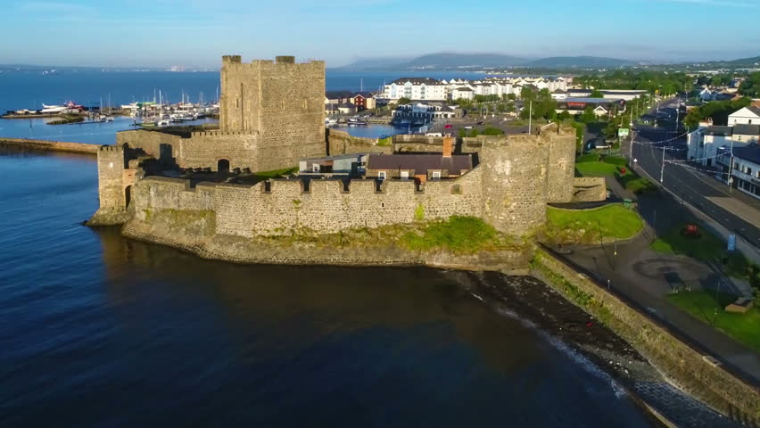 Medieval Norman Castle in Carrickfergus near Belfast, Northern Ireland,  in sunrise light. Aerial flyby video with marina, yachts, parking, town and far view of Belfast in the background | Shutterstock HD Video #31120459