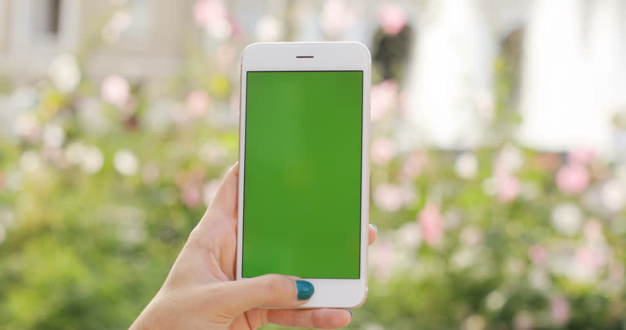 Woman hand holding using mobile smart phone blurred background plants garden green screen chromakey digital display closeup outdoor modern trendy lifestyle device hipster vertical keeping public space | Shutterstock HD Video #31126513