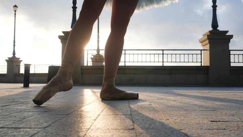 Close up of a ballet dancer's feet as she practices pointe exercises on the stone embankment. Woman's feet in pointe shoes. Ballerina shows classic ballet pas. Slow motion. Flare, gimbal shot #31129069