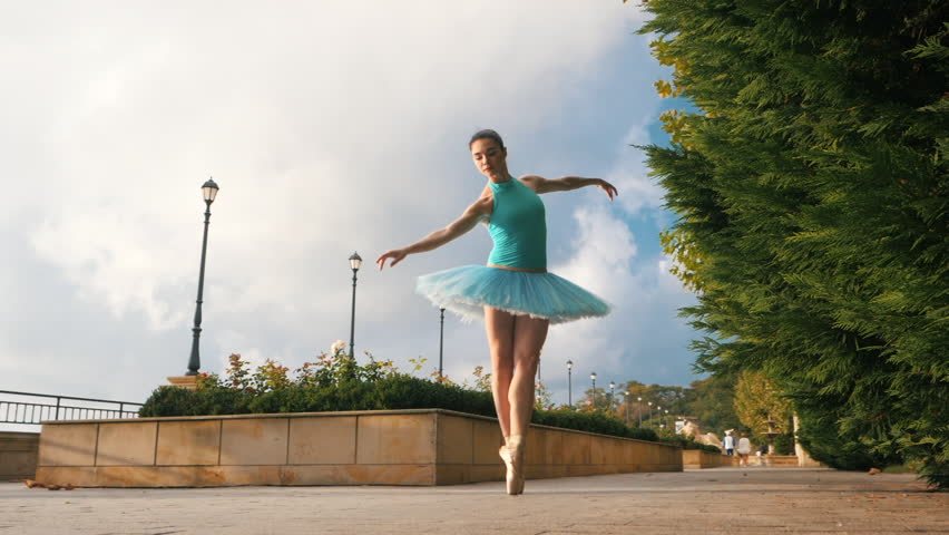 Dancing ballerina in blue ballet tutu and point on european street with trees in summer. Young beautiful brunette woman practicing stretching and exercises. SLOW MOTION. Flare, overall plan