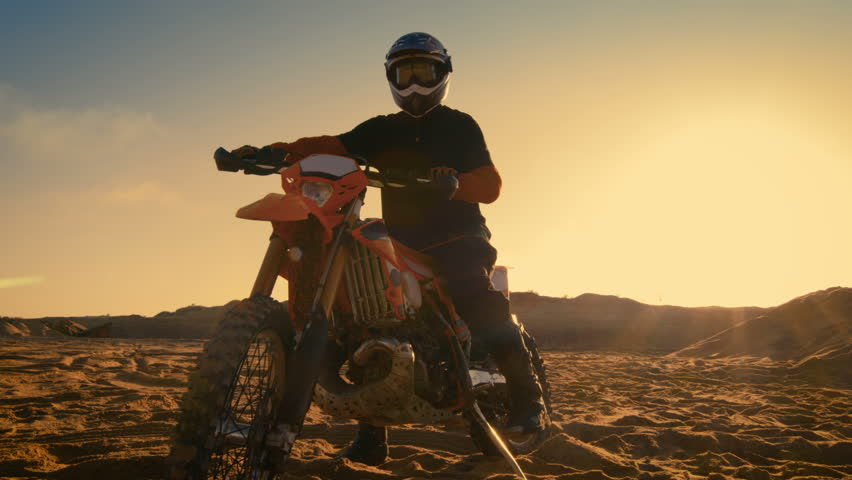 Low Angle Shot of the Professional Motocross Motorcycle Rider Standing on the Path of the Off-Road Track. It's Sunset and Track is Covered with Smoke/ Mist. Shot on RED EPIC-W 8K Helium Cinema Camera. | Shutterstock HD Video #31129444