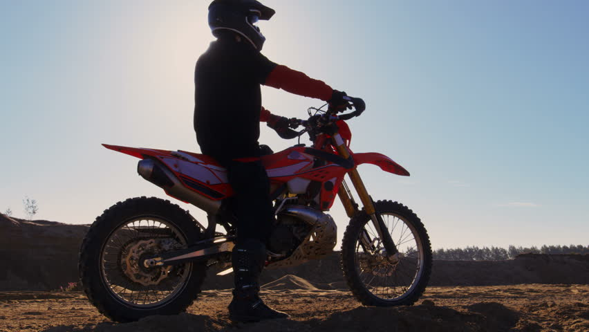 Side View Footage of the Professional Motocross Motorcycle Rider Driving on the Dune and Further Down the Off-Road Track. It's Sunset and Track is Covered with Smoke/ Dust/ Dirt. 4K UHD. | Shutterstock HD Video #31129522