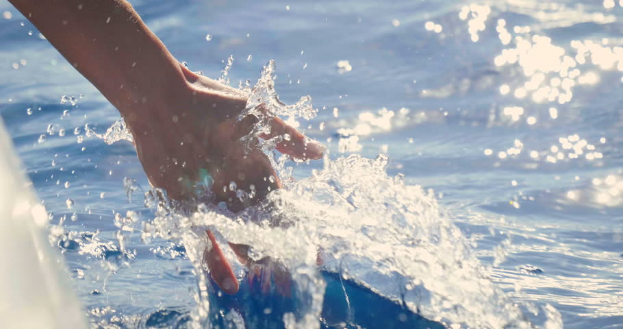 Slow motion of a female hand is touching a clear transparent water and enjoys the day at the sea alongside the waves of the boat. Concept of happiness, boat life and holidays in exotic places
