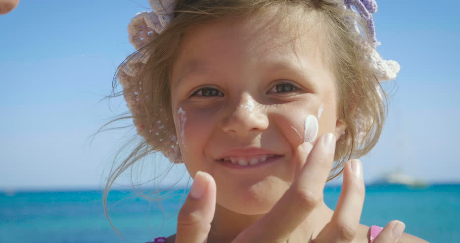 Portrait of beautiful little girl having fun on the sea, cute smiling in panama, sun protection cream, background of sea blue water and rocks. Concept: children, childhood, summer, freedom, kids, baby #31132684