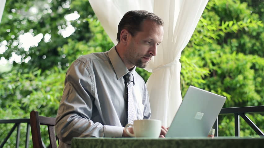 Businessman working on laptop and drinking coffee on balcony  | Shutterstock HD Video #3113503