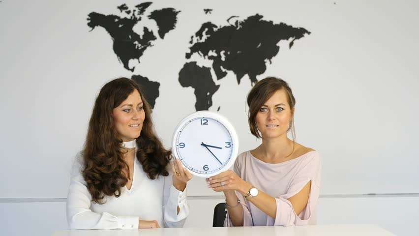 Two girls at the table in the studio holding a clock with arrows in their hands | Shutterstock HD Video #31141306