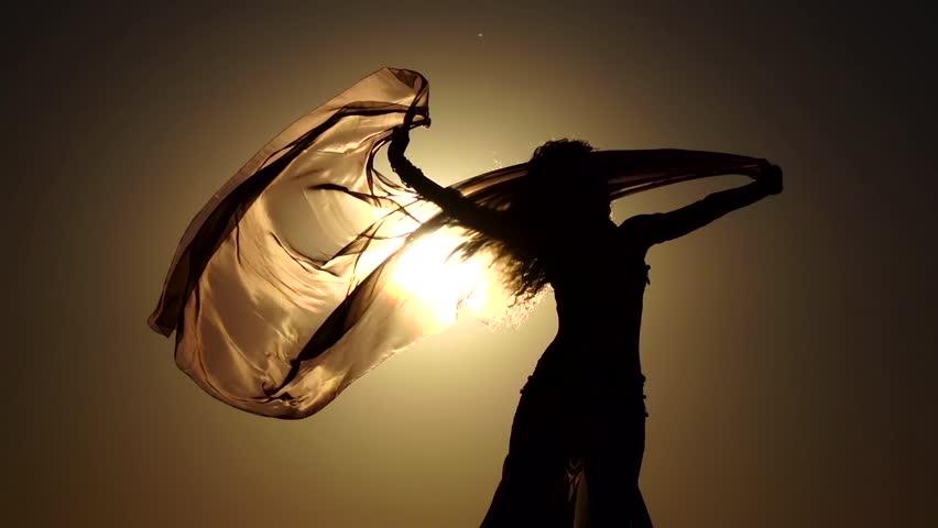 Girl on the seashore gracefully dances her body against the sunset. Silhouette. Slow motion