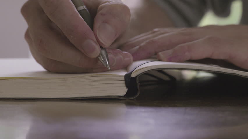 Notebook is opened and someone is writing a list or taking notes in it.  Royalty-Free Stock Footage #31153126