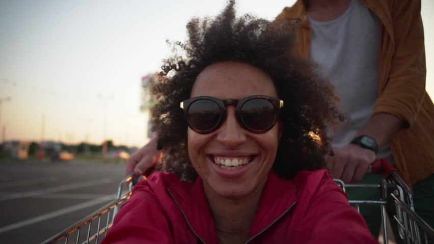 African american girl with curly hair making selfie video while caucasian bearded man circling her in shopping trolley in mall parking lot at sunset slow motion