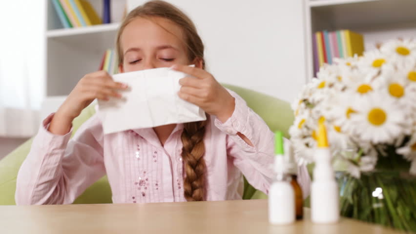 Girl with allergy blowing nose and sneezing - rack focus, sliding camera