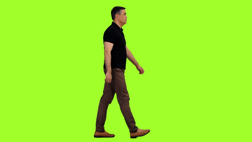 Side view of walking adult man on green screen background, Chroma key, 4k footage