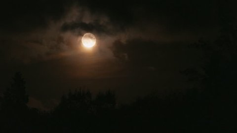 yellow moon through slow black clouds at night