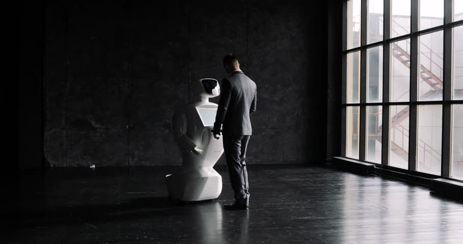 A stylish man communicates with a robot, presses a plastic mechanical arm to the robot, handshake. Cybernetic system today. Modern Robotic Technologies. Humanoid autonomous robot.