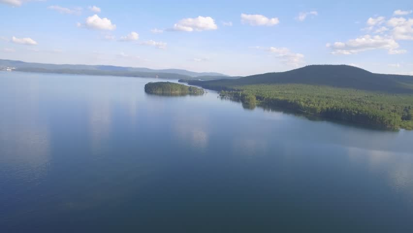 Aerial view of a remote tropical beach surrounded by forest. Aerial view of the lush Islands and lake. Flying Drone Above Beautiful Blue Sea Water. Wonderful Panoramic Landscape