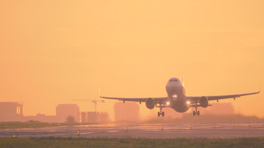 Airplane taking off at dawn. Aircraft takes off at sunset. Long shot