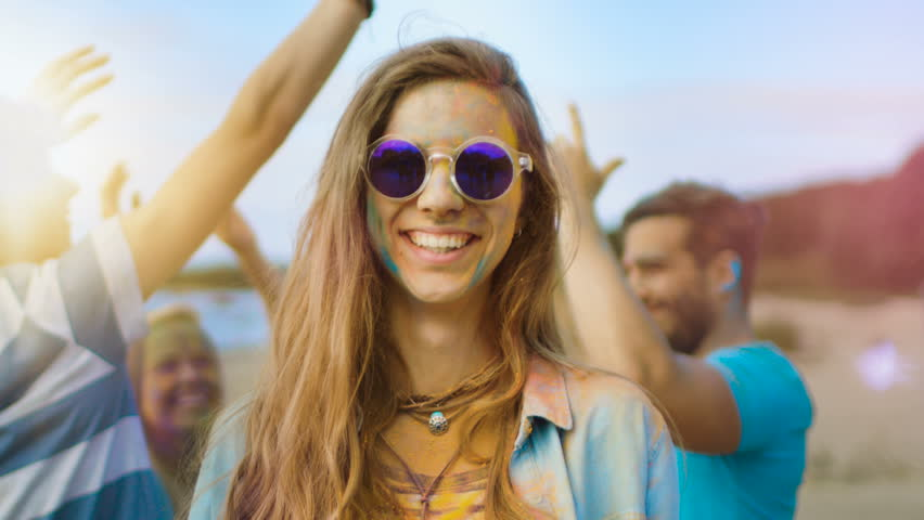 Close-up Portrait of a Beautiful Young Girl with Sunglasses Standing in the Crowd of People Celebrating Holi Festival. People Throwing Colorful Powder in Her Back. Shot on RED EPIC-W 8K Helium Camera.